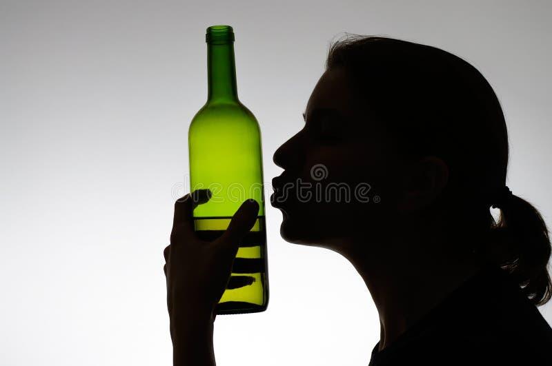 Alkoholiserad kvinna som kysser en vinflaska royaltyfria bilder