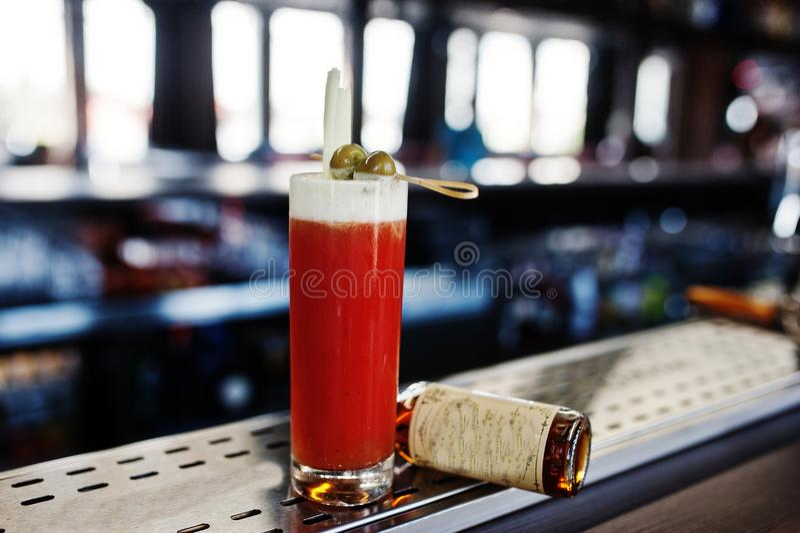 Alkoholiserad lång coctail med oliv i exponeringsglas på stångtabellen royaltyfri fotografi