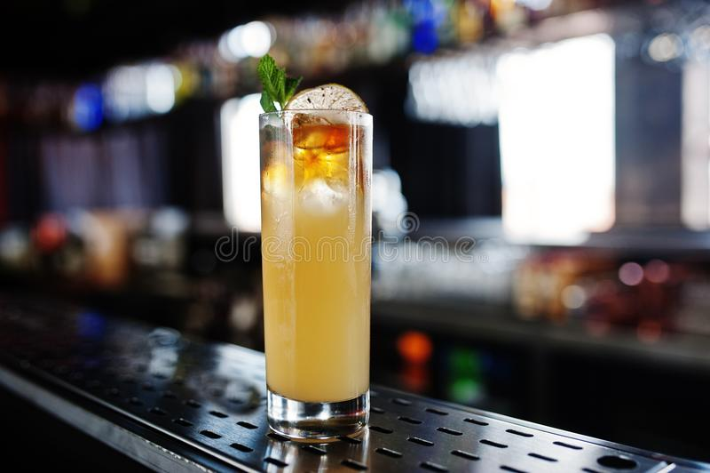 Alkoholiserad lång gul coctail i exponeringsglas på stångtabellen royaltyfria bilder