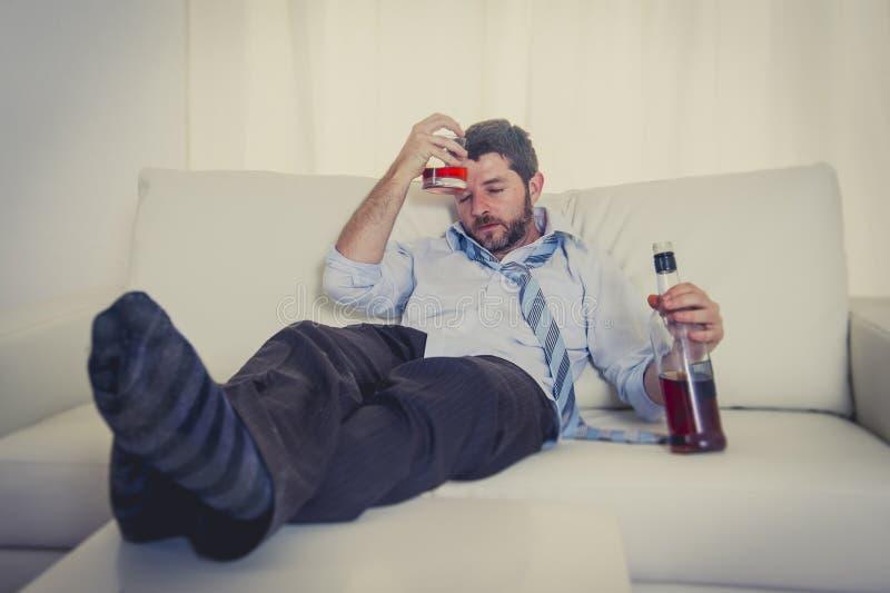 Alkoholiserade bärande blått för affärsman lossar bandet som drickas med whiskyflaskan på soffan royaltyfri bild