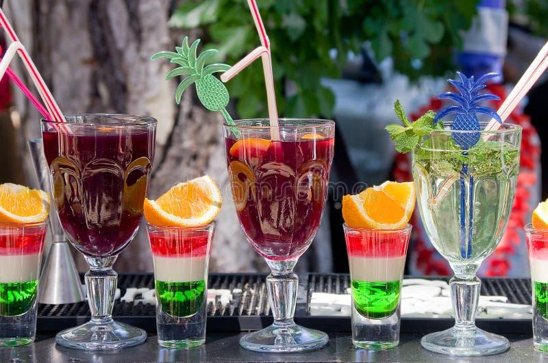 Alkoholiserade starksprit och mjuka uppfriskningdrinkar vid exponeringsglaset på stången utomhus royaltyfri bild