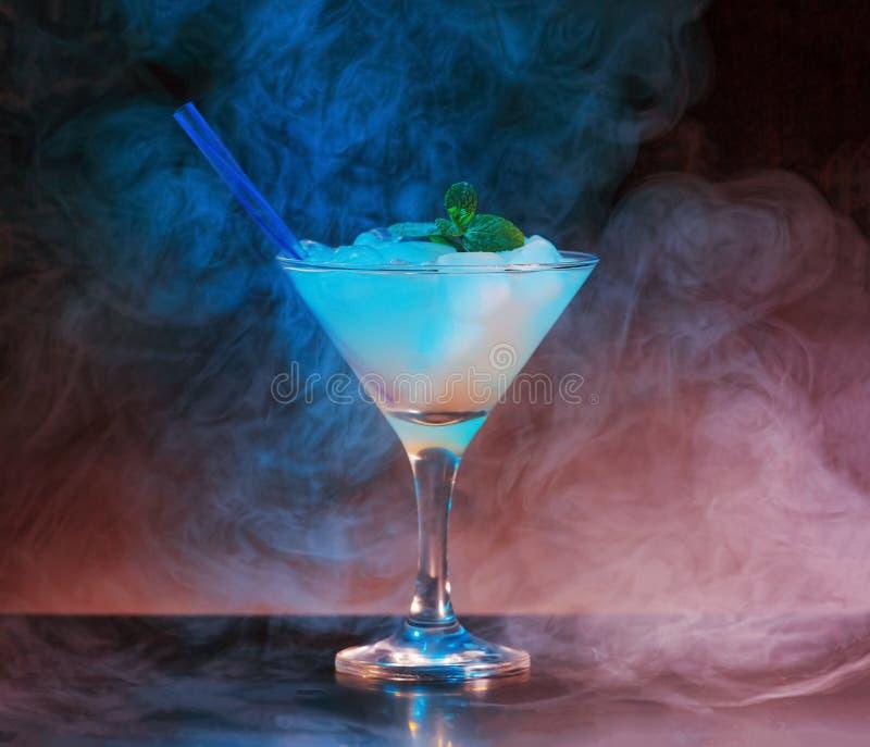Alkoholist coctail, dramatisk inre, rök, reflexion som är violett, kroppsligen arkivbild