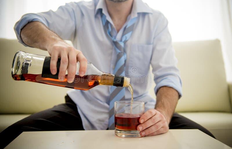 Alkoholist drucken affärsman i lös tid på soffan som dricker whisky arkivfoto