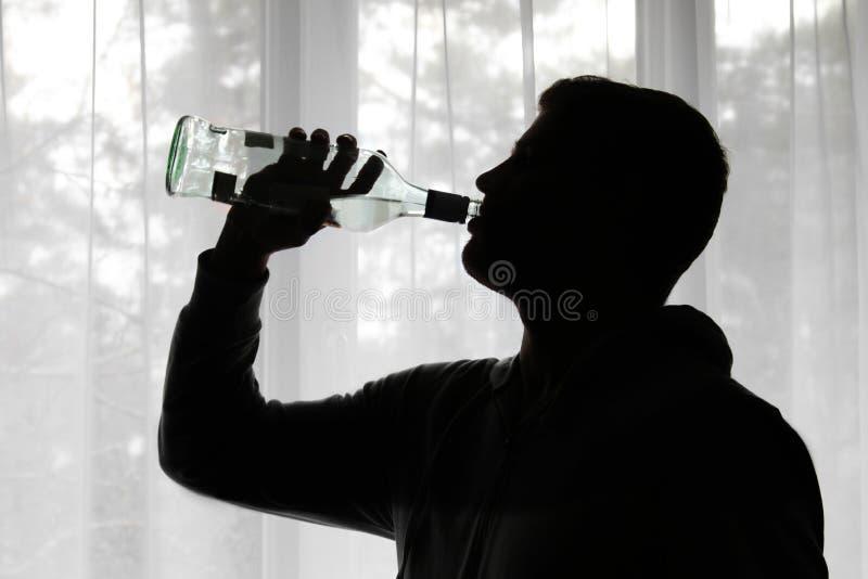 Alkoholizm - sylwetka pije alkohol mężczyzna zdjęcie royalty free