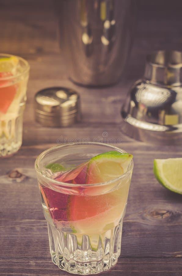 Alkoholschüsse mit einem Kalk/Alkoholschüsse mit einem Kalk auf einem Holztisch stockfoto