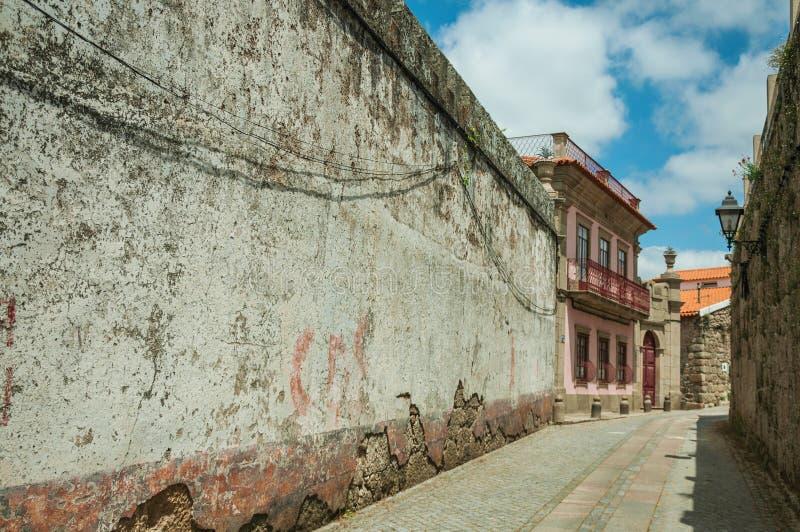 Allée avec le mur usé de plâtre et la vieille maison photographie stock libre de droits