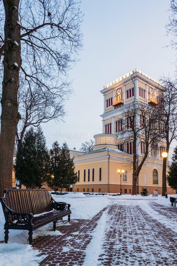 Allée d'hiver avec un banc et une tour d'horloge en parc Gomel, Belarus photos stock