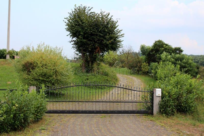 Allée en pierre de tuiles menant à la porte noire de fer travaillé montée sur deux poteaux concrets entourés avec l'herbe verte n photo stock