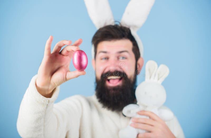 Allí va Inconformista con los oídos de conejo largos que sostienen las liebres de la colocación de huevo Hombre barbudo con el ju fotos de archivo