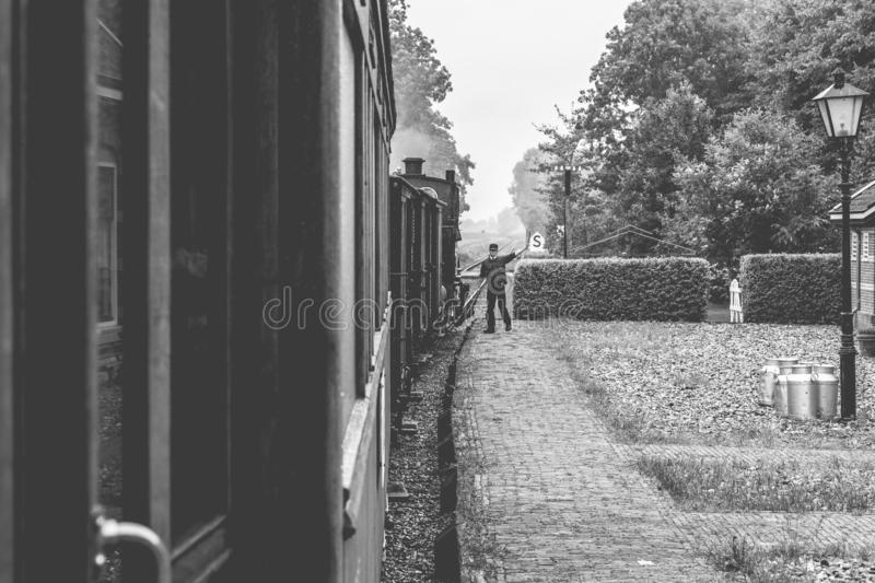 Steam Train Bygone Era. Authentic steam train adventures through the north of Holland. Bygone era including conductor on platform royalty free stock images