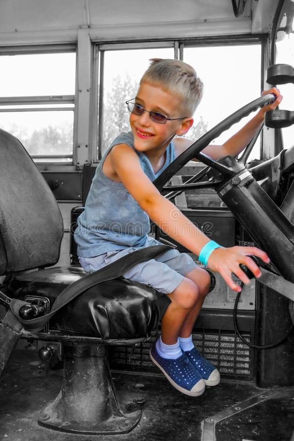 Child Pretend Drive Bus. All aboard the school bus. Young boy beckons riders to join him on the bus. Pretend playtime royalty free stock image
