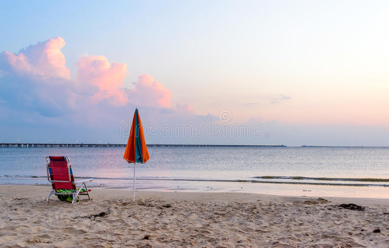 All Alone. Beach chair and umbrella alone on the beach with the Chesapeake Bay Bridge in the background. Located on the Cheaspeake Bay, Virginia Beach side stock photography