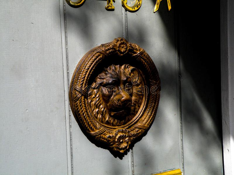A Brass Door Knocker Hangs on the Door of a Home in the New Orleans French Quarter. All around New Orleans French Quarter you will find all types of art royalty free stock photos