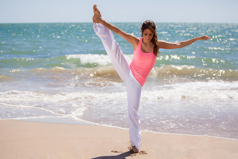 It is all about balance. Beautiful Hispanic woman trying to keep balance for a yoga pose at the beach royalty free stock photos