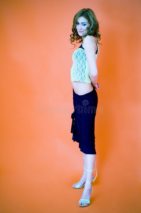 All dressed up. Young woman all dressed up in party clothes and heels strikes a pose. Portrait orientation royalty free stock photo