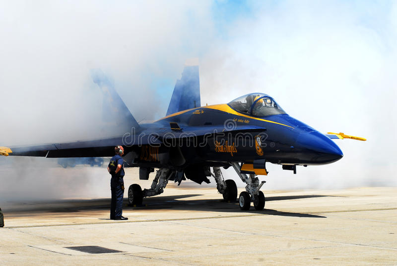 All Fired Up. Crewman for the U.S. Navy Blue Angels mans his post as the #2 pilot fires up his engine prior to performing stock photo