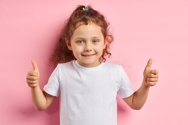 All is good. Beautiful caucasian kid raised thumbs up. Smiling girl 5 years old thumbs up, looking at camera. Wearing white t-shirt, stand isolated over pink stock photography