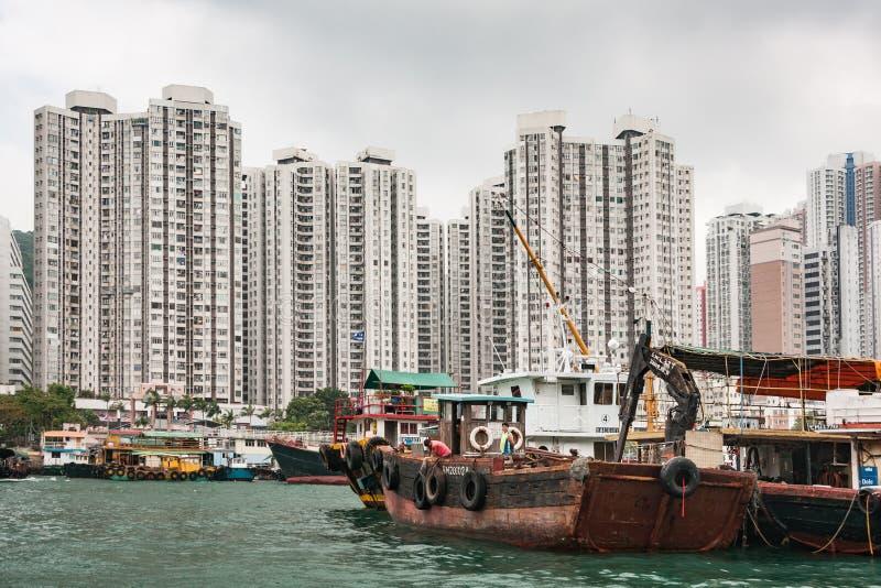 All kind of boats in front of tall buildings in harbor of Hong Kong, China. Hong Kong, China - May 12, 2010: All kind of boats in the harbor with tall apartment royalty free stock photo