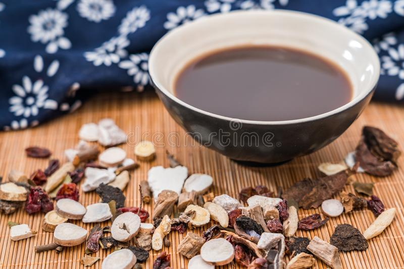 All kinds of traditional Chinese medicine and a bowl of traditional Chinese medicine soup scattered on the bamboo mat stock image