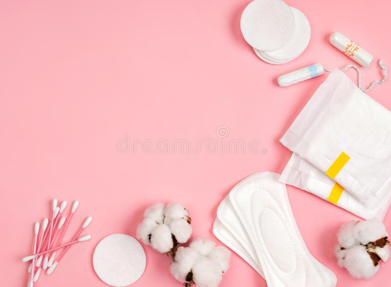 All made of cotton. Hygiene accessories - sanitary napkins, cotton pads, cotton swabs, tampons on pink background. Concept of critical days, menstruation royalty free stock images
