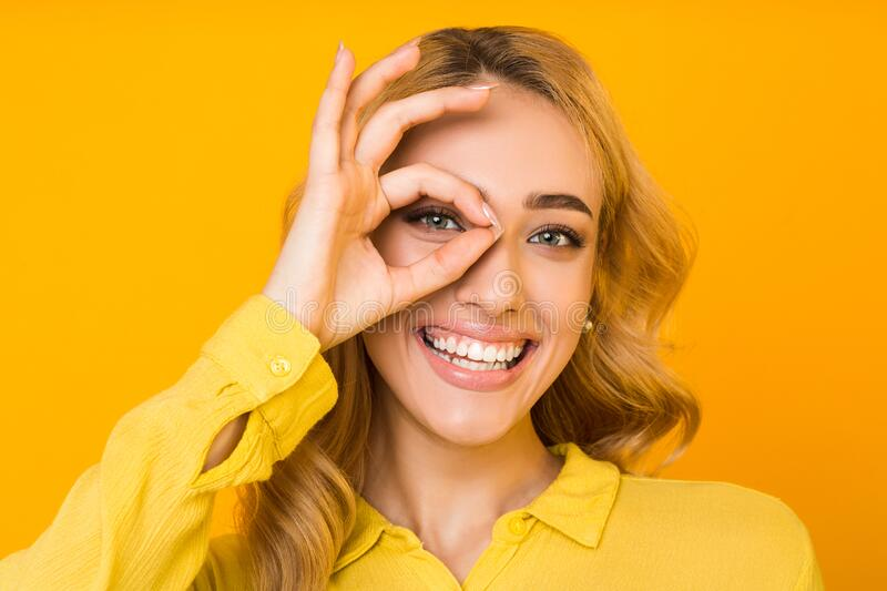 All is ok. Girl gesturing okay sign with hand on eye. And widely smiling over yellow background stock photo