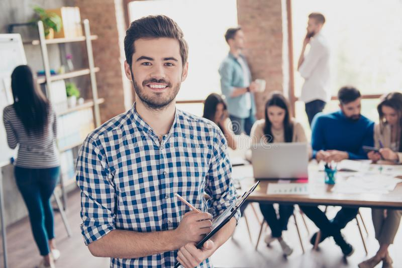 All for one and one for all! Leadership. Successful stylish young bearded man in casual checkered shirt is standing in the office stock images