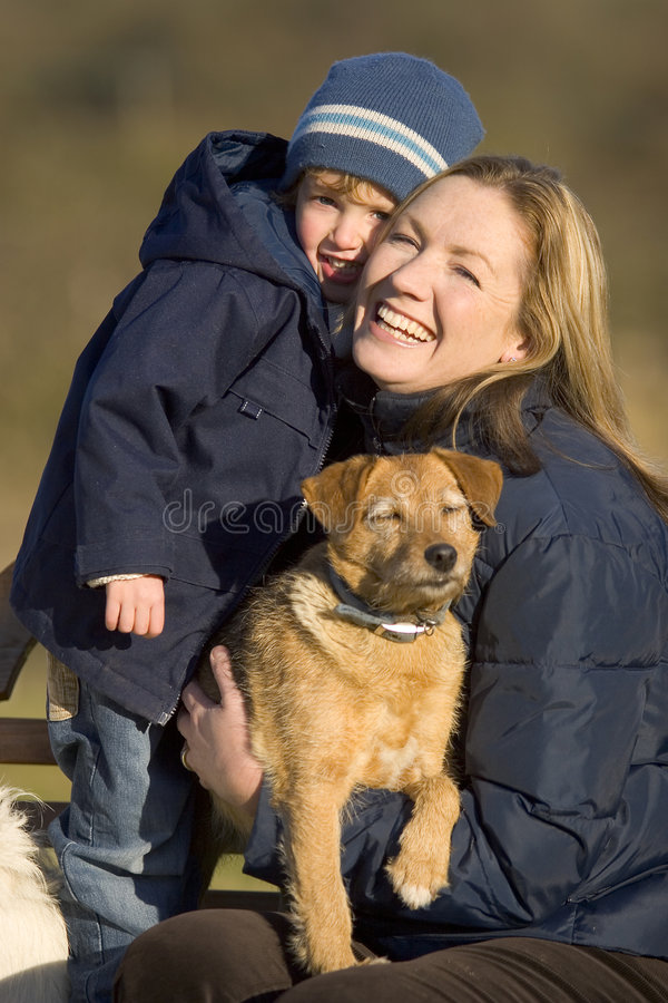 All Part Of The Family. A mother her young son and the family dog cuddle up in the winter sun