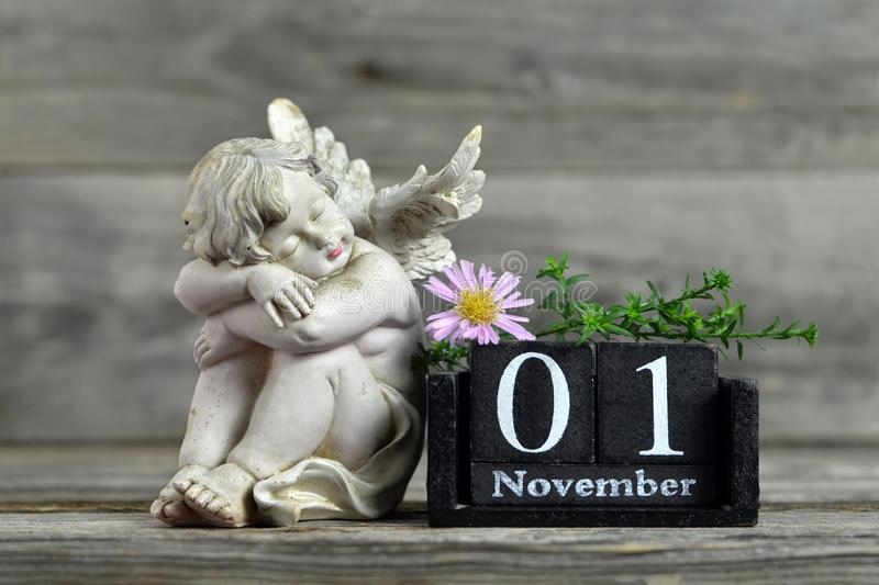 All Saints Day. Angel, wooden calendar and flower. All Saints Day. Angel, wooden calendar and aster flower royalty free stock image