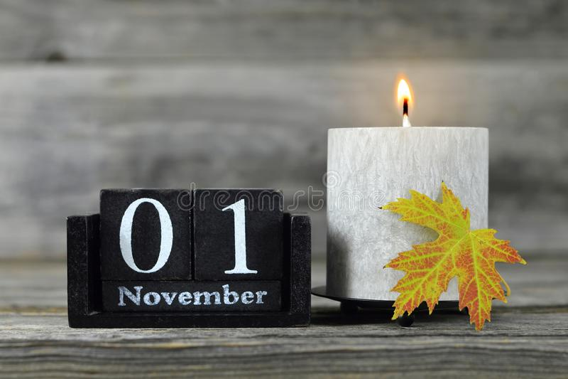 All Saints Day. Burning candle, wooden calendar and yellow autumn leaf. All Saints Day. Burning candle, wooden calendar and  autumn leaf royalty free stock images