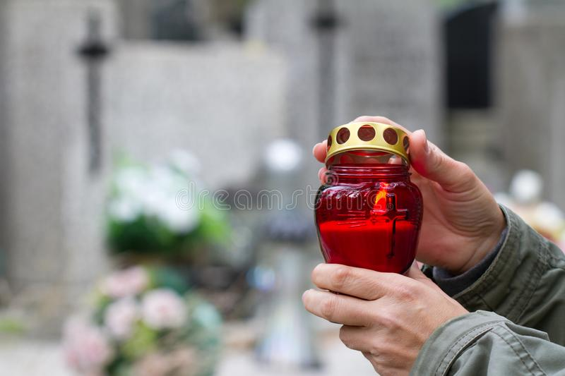 All Saints` Day and christian hands with candle light of memory on cemetery. Background concept royalty free stock photos
