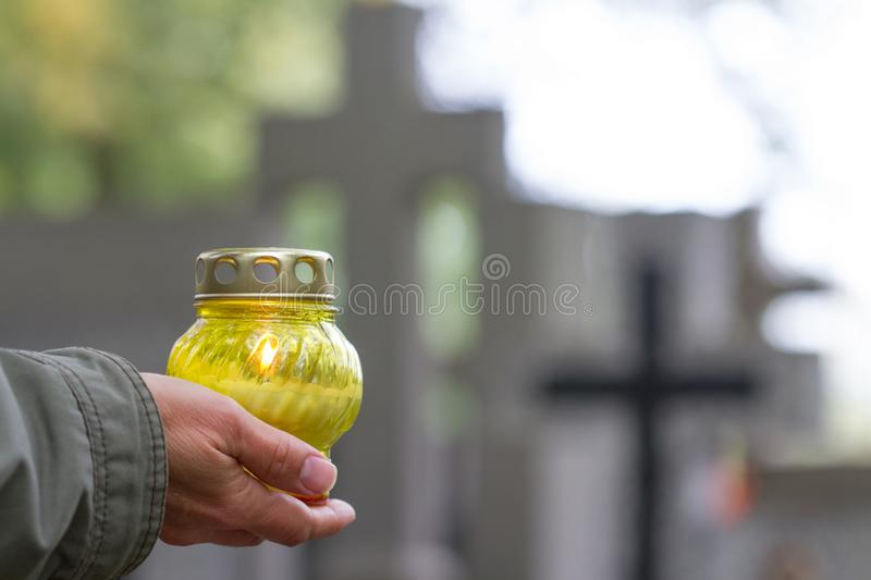 All Saints` Day and christian hands with candle light of memory on cemetery. Background concept royalty free stock images