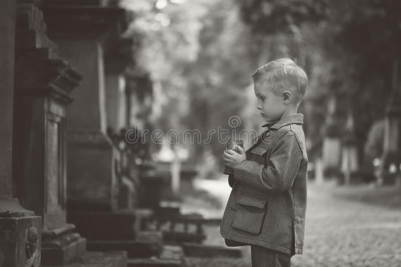All Saints` Day. Memory of the dead. All Saints` Day. In the old cemetery, a boy with a candle. Sad and thoughtful. Polish tradition and feast dedicated to all royalty free stock images