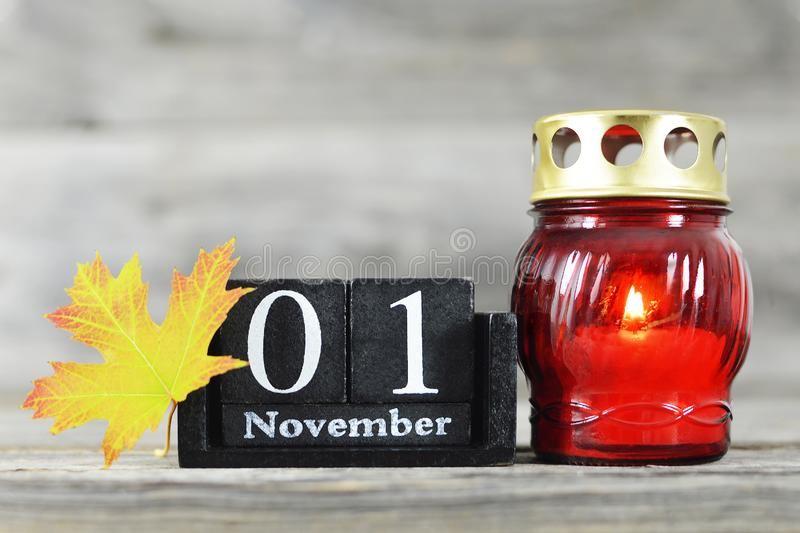 All saints Day. Votive candle, wooden calendar and yellow autumn leaf. All saints Day. Red votive candle, wooden calendar and yellow autumn leaf stock photography