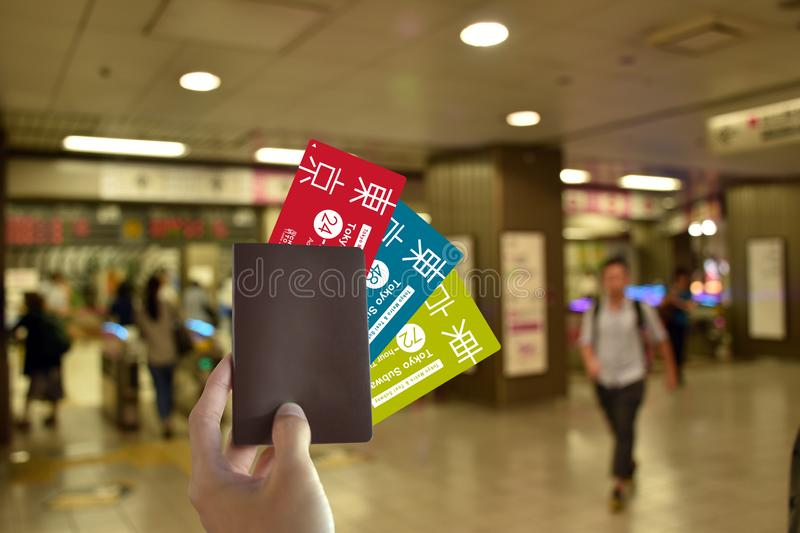 Hand with blank Passport and all subway card of japan to travel in Tokyo on blurred subway background royalty free stock images