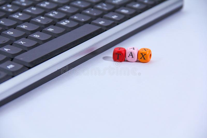 Tax on wooden block and keyboard with tax alphabet stock photography