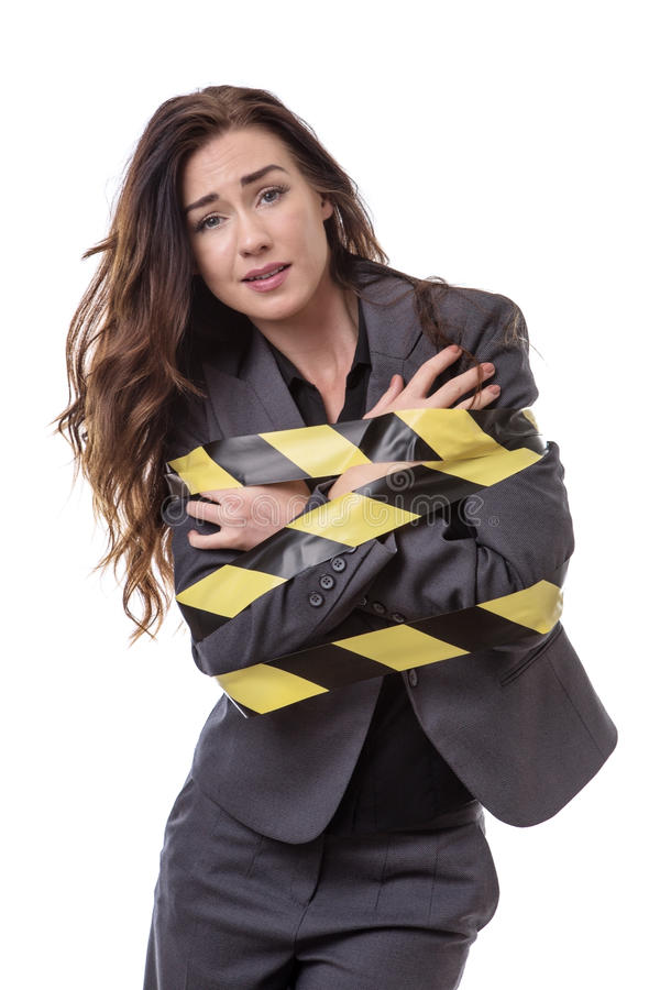 All tied up!. Business woman wrapped up in yellow and black tape isolated on white royalty free stock photo