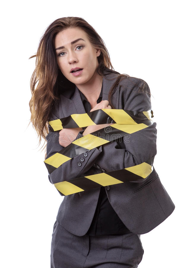 All tied up!. Business woman wrapped up in yellow and black tape isolated on white stock photo