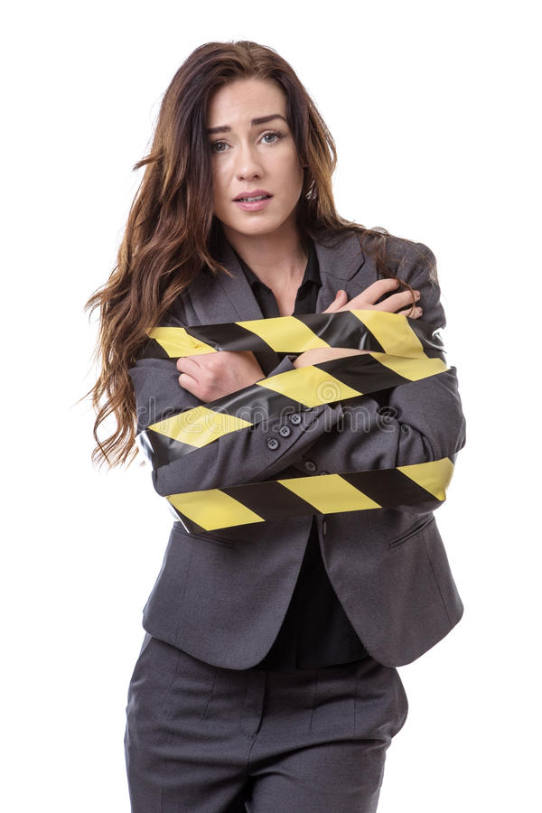 All tied up!. Business woman wrapped up in yellow and black tape isolated on white royalty free stock photos