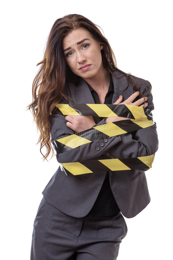 All tied up!. Business woman wrapped up in yellow and black tape isolated on white royalty free stock image