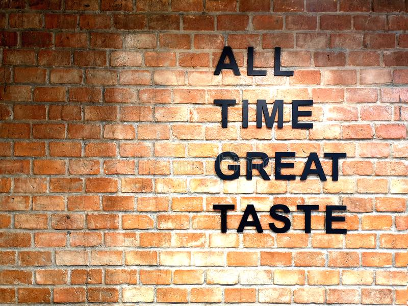ALL TIME GREAT TASTE banner lettering on red, old orange brick wall background. Space for copy, text royalty free stock image