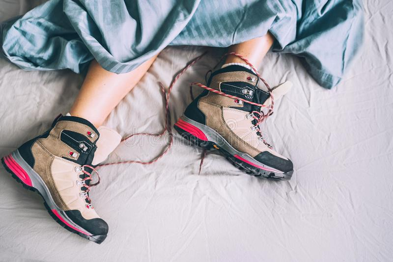 All time ready for trekking. Hiker female sleeping in comfort trekking boots. Footwear on the bed sheet background concept image. stock image