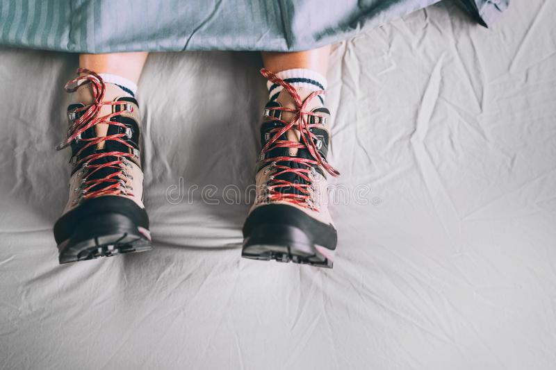 All time ready for trekking. Hiker sleeping in comfort trekking boots. Footwear on the bed sheet background concept image stock photos