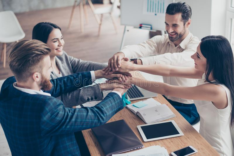All together! Happy businesspeople putting their hands on top of stock image