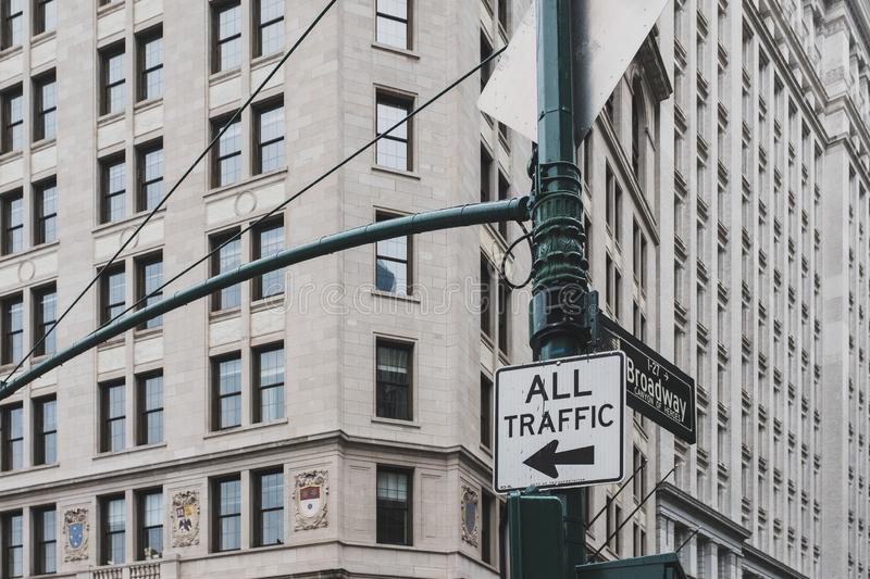 All traffic to left sign and Broadway street name sign on a street lamp post, against exterior of building in lower Manhattan royalty free stock images