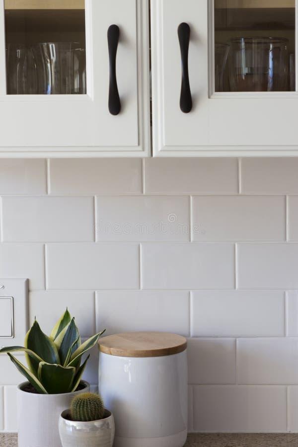 All vit köksskåp, tegelplatta och dekor arkivbild