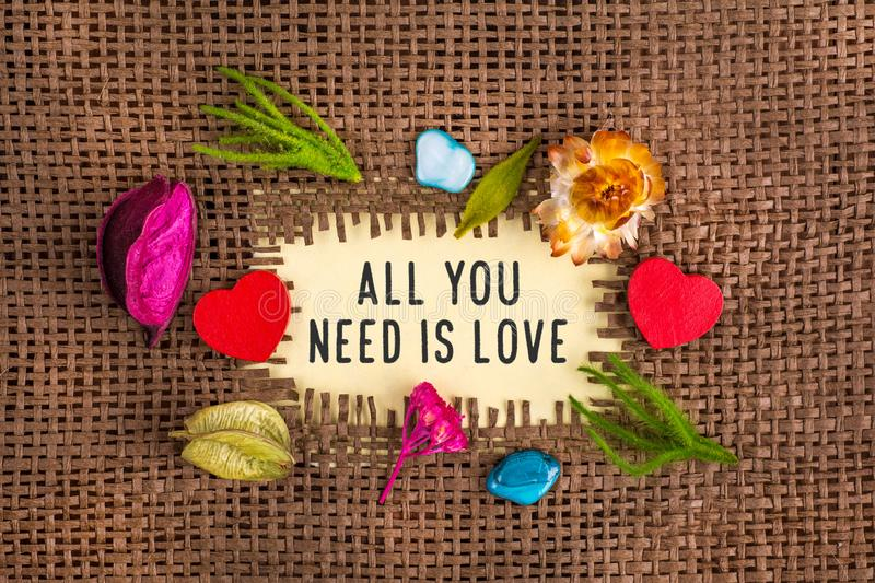All you need is love written in hole on the burlap. All you need is love now written in hole on the burlap with dried flowers and wooden red heart and blue stone stock images