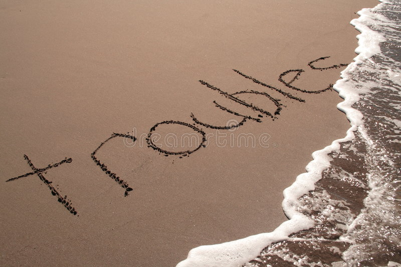 All your troubles will just wash away... Troubles written on the beach about to get washed away stock images