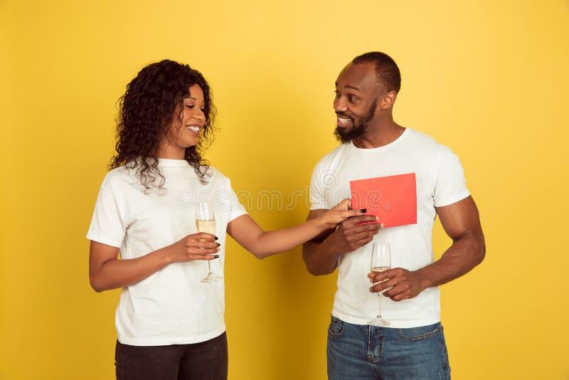 Alla hjärtans dag firas, ett lyckligt afrikanskt par isolerat på gul bakgrund royaltyfri bild