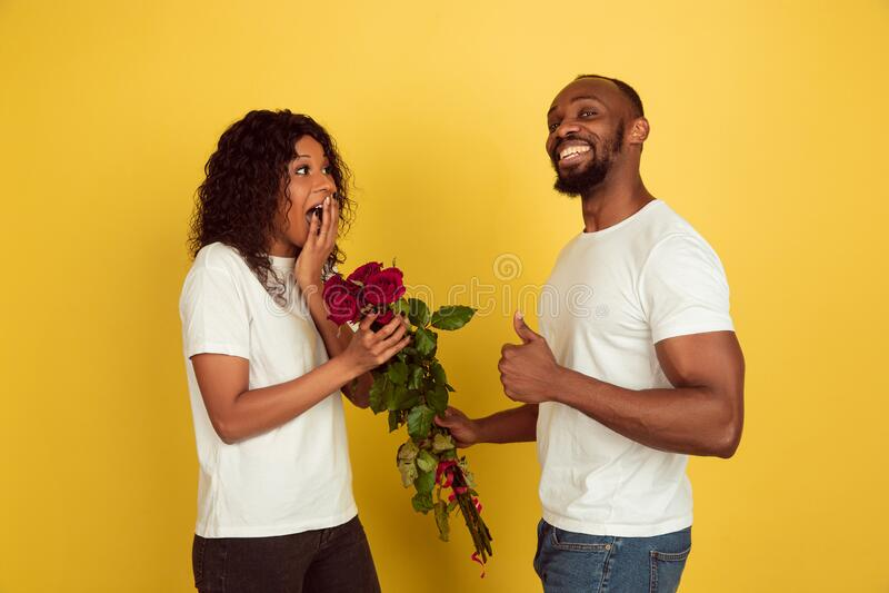 Alla hjärtans dag firas, ett lyckligt afrikanskt par isolerat på gul bakgrund royaltyfri fotografi