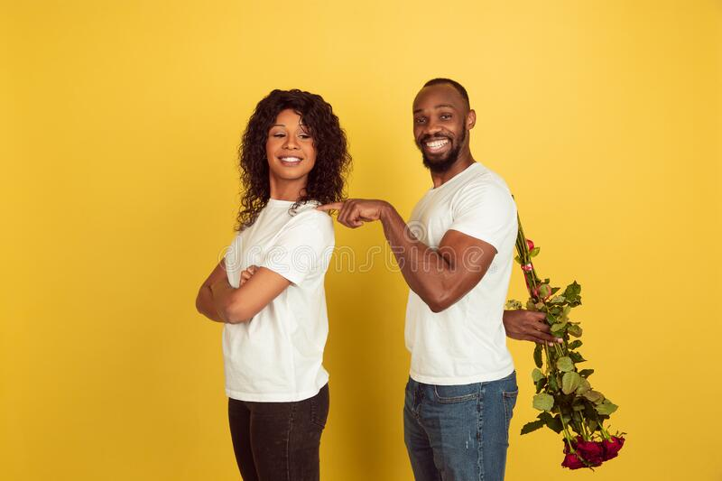 Alla hjärtans dag firas, ett lyckligt afrikanskt par isolerat på gul bakgrund arkivfoton